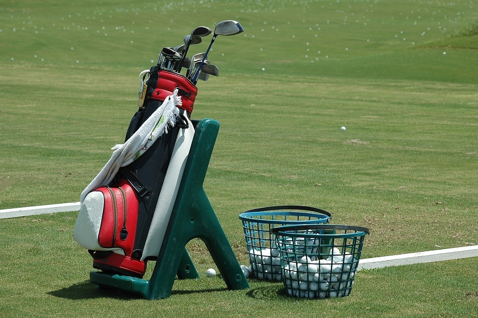 a golfing carry bag near two baskets filled with golf balls